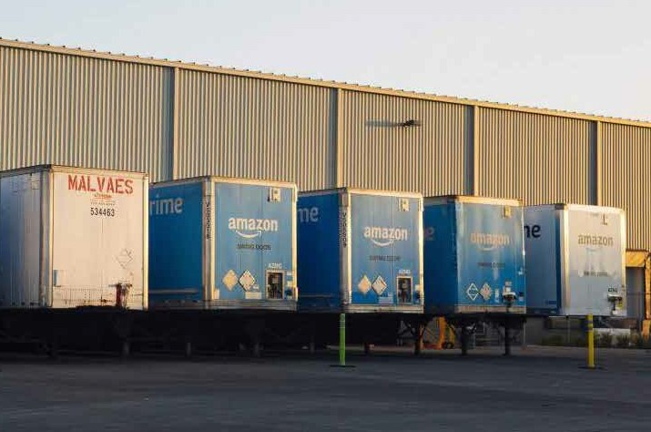 A rank of Amazon tricks waiting to be loaded at a distribution warehouse, available for commercial investment.