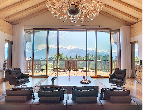 Intérieur d'un appartement en duplex avec un beau lustre et une vue luxueuse sur les montagnes à travers les immenses baies vitrées et le balcon.