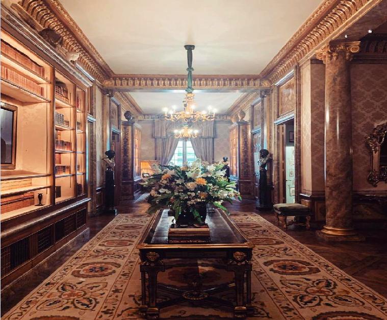 Intérieur d'appartement luxueux avec meubles et tapis du 18ème siècle, plafonds dorés et piliers en marbre.