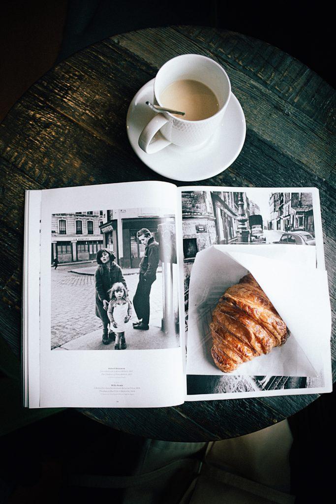 Photo d'un croissant chaud assis sur un magazine noir et blanc avec un café crémeux, à une table de café.