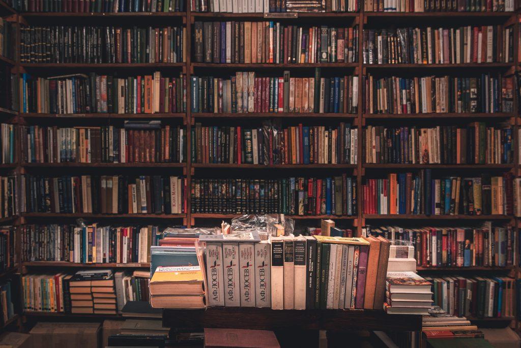 Image de l'intérieur d'une librairie traditionnelle avec des murs recouverts de livres d'occasion colorés, et une table devant remplie de livres également.