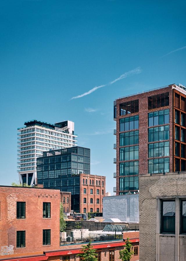 Вид на здания разных стилей в Бруклине: исторический стиль, невысокое здание из красного кирпича впереди и современные стеклянные здания на заднем плане.